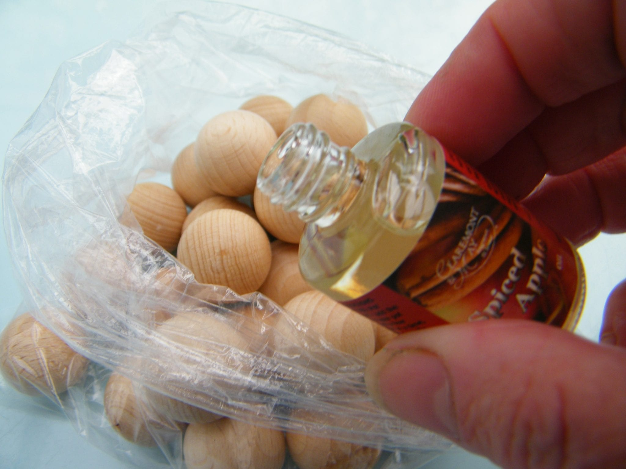 Adding fragrance oil to wooden balls