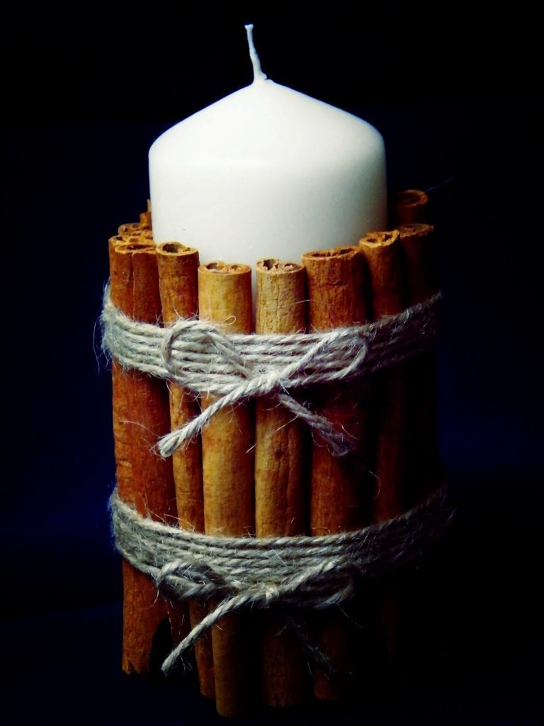 decorating candles with cinnamon sticks