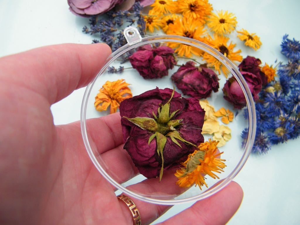 placing flowers in christmas bauble